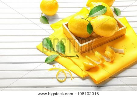 Wooden crate with juicy citrus fruit, green leaves and lemon zest on wooden table