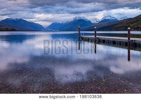 The dock on Lake MacDonald in Glacier National Park in Montana, USA on a n overcast day in late afternoon light in autumn.