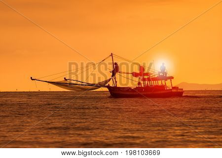 silhouette photography of fishery boat and sunset sky over sea horizontal
