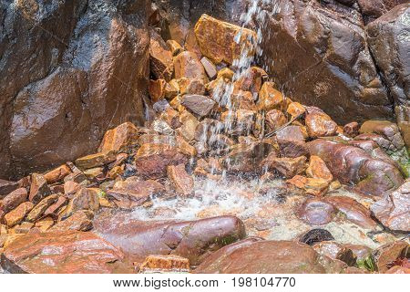 Small Waterfall Among Rocks And Stones In Moss
