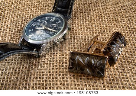 Cuff links and metal watch with the round dial and a black leather thong lie on a sacking. Horizontal format. Indoors. Color. Photo.