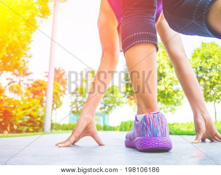 Ready steady go. Closeup of running shoes on grass young lady on start position and going to run in park.
