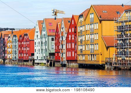 Famous wooden colored houses in Trondheim city Norway. Colorful houses on stilts in sunny day.