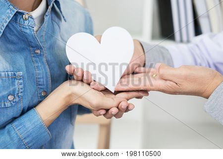 Charity, Health Care, Donation And Medicine Concept - Doctor Man Hand Giving Heart To Patient