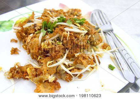 Oysters fried in egg batter in a white dish with spoon and mug