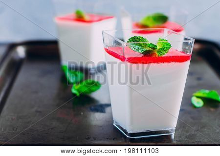 Delicious Italian dessert Panna Cotta with raspberry sauce coulis served for three in small transparent glasses. Summer sweet desser