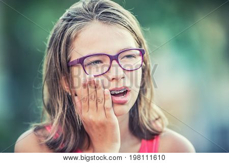 Portrait Of Young Teen Girl With Toothache. Girl With Dental Braces And Glasses