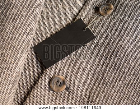Blank black label price tag on brown coat. Mockup for price or brand presentation.