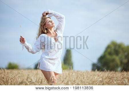 Woman enjoys nature in a wheat field she enjoys and relaxes.