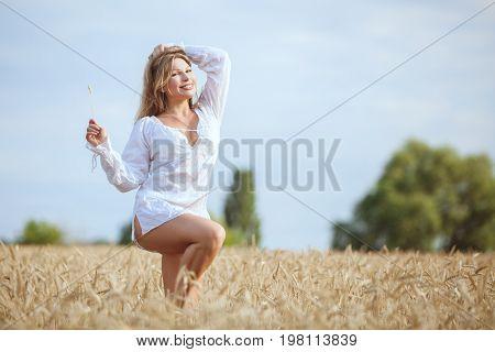 Happy woman in a wheat field enjoys freshness.