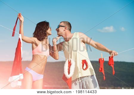 Couple of happy man and girl hanging clothes for drying. Laundry and dry cleaning. Xmas red costume on rope with pin. Christmas man and woman family. New year guy with muscular body on blue sky.