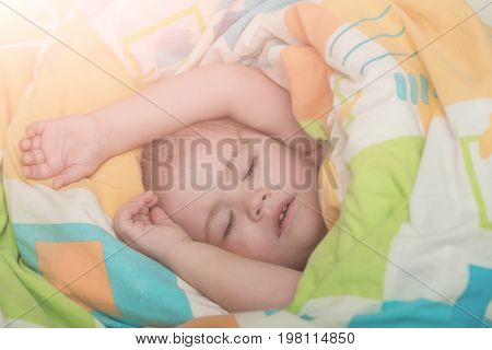 Child sleep in bed. Childhood and happiness. Small baby dreaming. Trust and tenderness. Sleepy baby in colorful blanket.