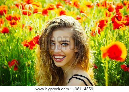 woman. happy smiling girl with long curly hair hold flower in field of red poppy seed with green stem on natural background summer spring drug and love intoxication opium