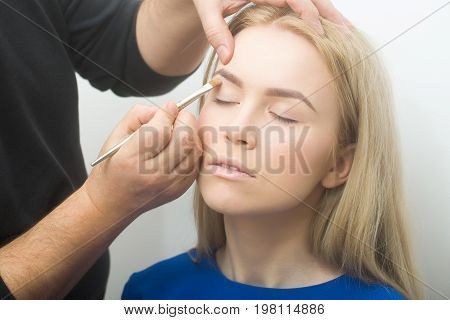 Hands applying concealer on girl eyelids with makeup brush. Pretty woman with closed eyes young healthy face skin and long blond hair in beauty salon. Visage make up cosmetics and skincare