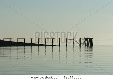 silhouette of a stand up paddle boarder looking small next to a long wooden pier