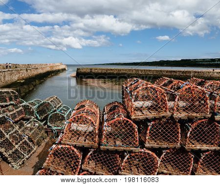 tall stacks of lobster traps on a harbour in Scotland with a long pier streching out to sea