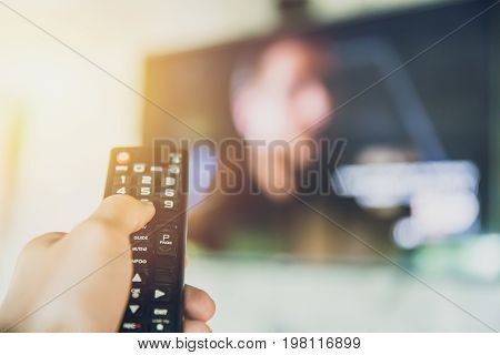 hand hold Smart TV remote control with a television blur background. change watching program channel