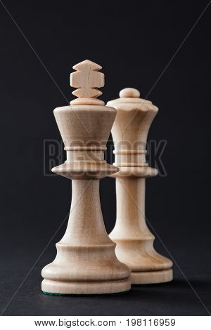 Wooden chess pieces figures white king and queen isolated on black colored background.