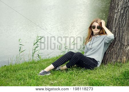 Pretty teen girl with long blonde hair relaxing under the tree in the park. Beauty, fashion. Teen style.