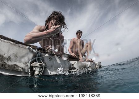 Two men floating in the tropical sea and waiting for rescue