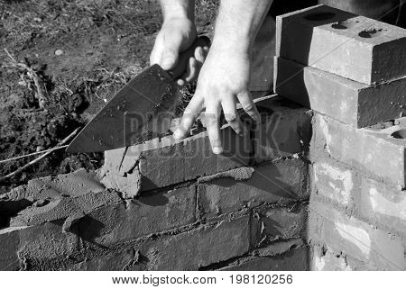 Closeup of bricklayer building a house extension. Photo shows man holding trowel while laying bricks.