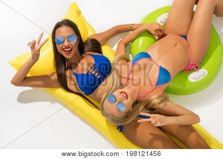 Sexy girls wearing sunglasses and blue bicinis lying on yellow swimming air mattress shot from above isolated