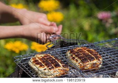 Top view on two grilled slices of homemade halloumi cheese on grill in woman's hands. Outdoors. Grilling season.