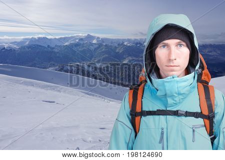 Portrait of young man mountaineer in the winter mountains. Blue sky and white clouds
