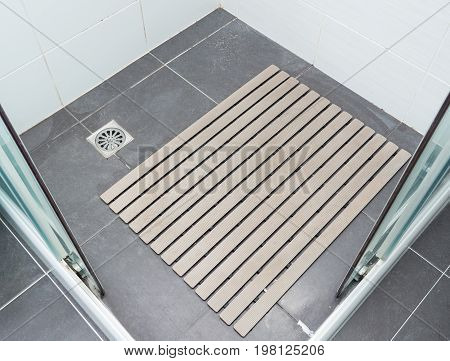 Rubber slip pad with the many hair pieces in the shower stall of the modern house.