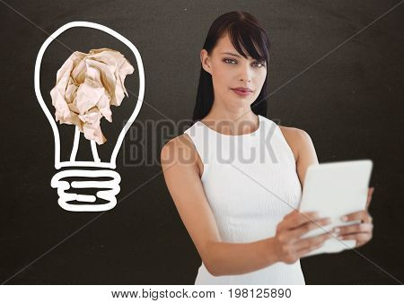 Digital composite of Woman with tablet standing next to light bulb with crumpled paper ball in front of blackboard