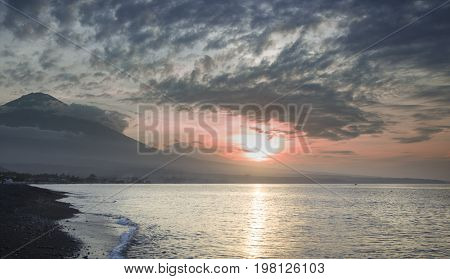 Amazing sunset closed to the sea. It is Agung Volcano on the background. The sun is setting into the water.