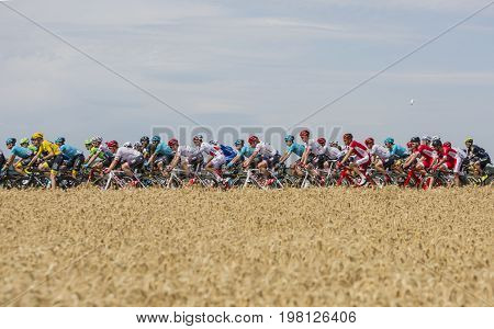 Vendeuvre-sur-Barse France - 6 July 2017: A cyclist's water-can flies over the peloton passing through a region of wheat fields during the stage 6 of Tour de France 2017.