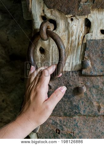 Woman's hand holds the ring of the ancient gate of the castle. Ancient gate. Gate in the historical museum.