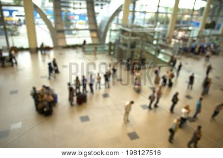 Airport. Blurred people in the main lobby closed to fly announced desk. They are in big city airport.