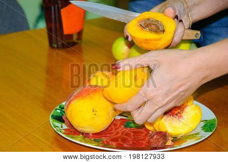 Hands Are Cutting Peaches Over A Plate