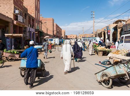 Rissani Morocco - May 09 2017: Moroccan vendors deliver fresh fruits and vegetables in their push carts to the food stalls while the locals are shopping on a sunny morning in Rissani Morocco.