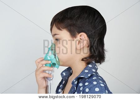 Boy using asthma machine on light background