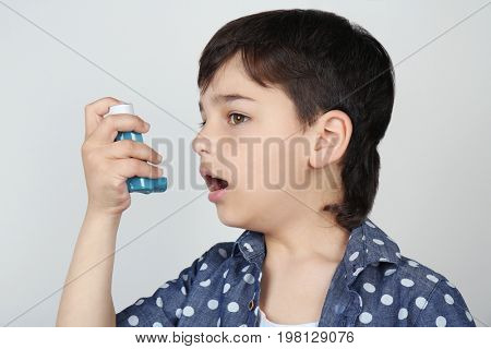 Boy using inhaler during asthmatic attack on light background