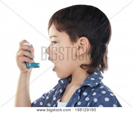 Boy using inhaler during asthmatic attack on white background