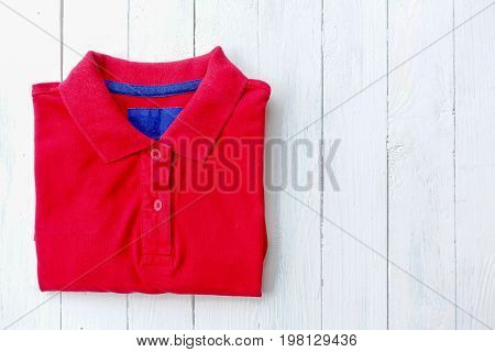Red polo shirt put on white wooden tabletop