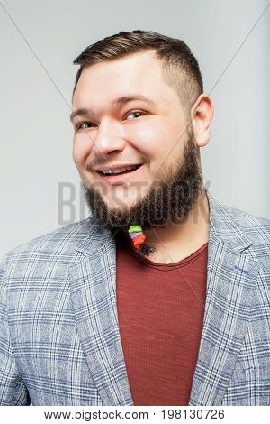close up portrait of young happy fat man with hair clips on long beard over gray background. Concept of comic, hairdo, hair style