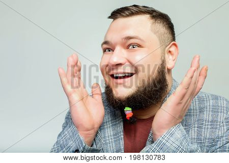 close up portrait of handsome happy fat man with hair clips on long beard over gray background. Concept of comic, hairdo, hair style