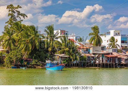 Vietnamese homes on the riverbank of the cai river with a fishing boat and a cloudy sky in Nha Trang Vietnam.