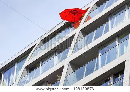 Red parasol on a modern apartment building balcony in Rotterdam in the Netherlands