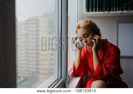 Beautiful Young Girl In The Early Morning By The Window In Silk Red Pajamas
