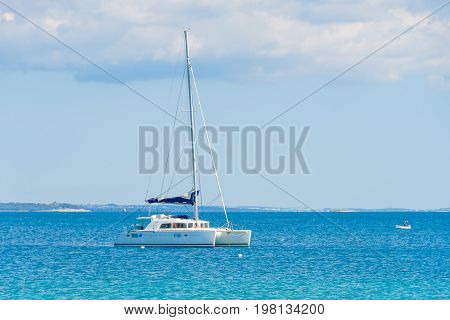Luxury sailing catamaran in open sea, anchored in shallow water, against plain horizon with clouds