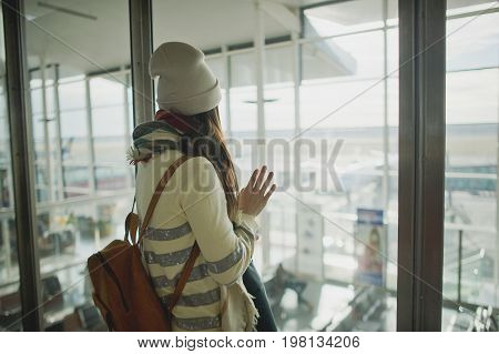 A woman with a backpack standing at the large window in the airport. She is watching the airplanes on the airfield.