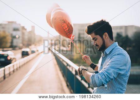 Sad unhappy man waiting for girlfriend on valentine date