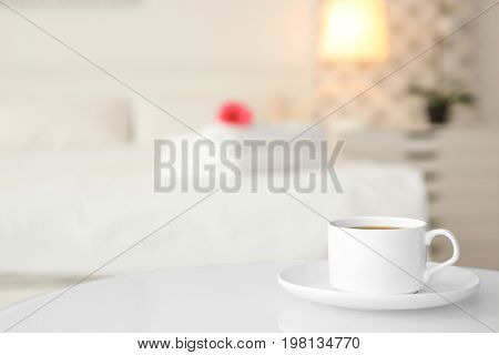 Cup of coffee on white table in light hotel room