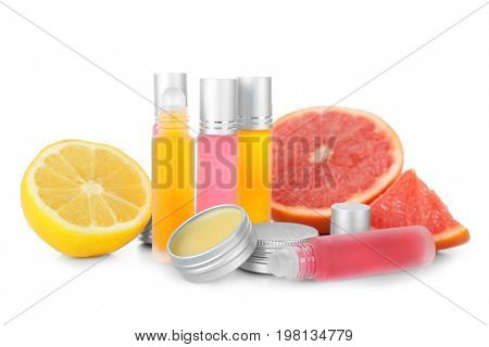 Bottles and jars with perfume near fresh citrus fruits on white background